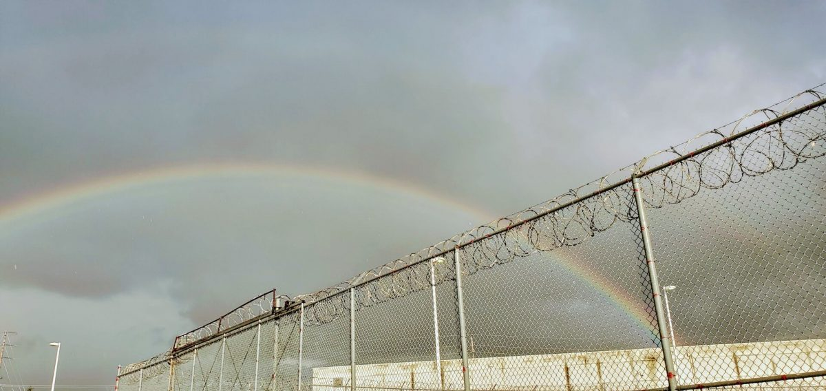 A rainbow arcs above the barbed wire fence of an ICE Detention Center